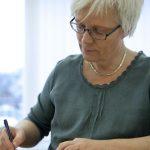 Frau sitzt am Schreibtisch und schreibt konzentriert