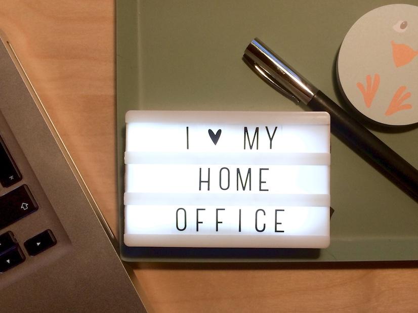 """Eine kleine Lightbox mit dem Spruch """"I love my Home-Office"""", Schreibutensilien und ein Mac auf dem Schreibtisch"""