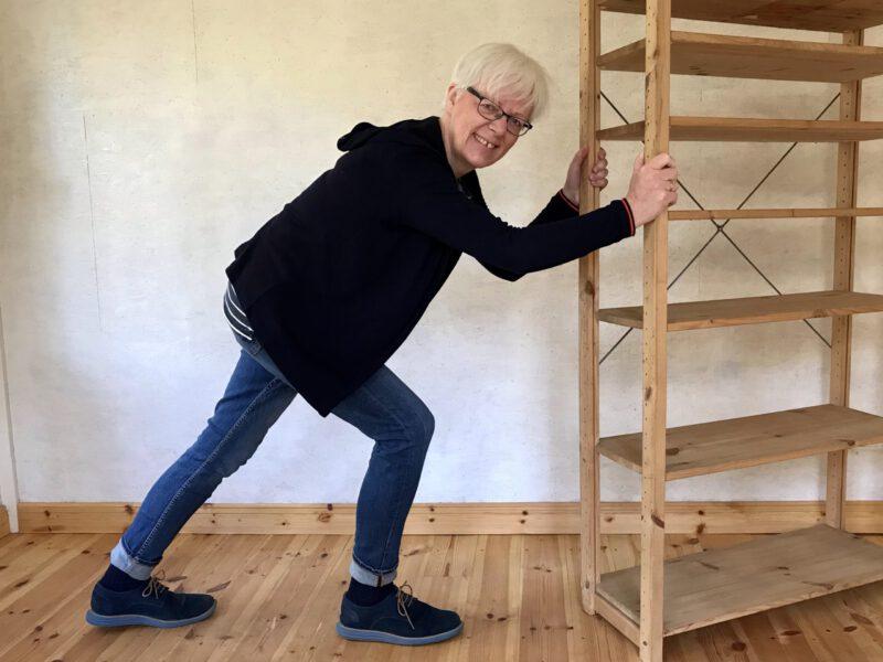 Katrin Gerke schiebt ein leeres Holzregal vornübergebeugt mit vollem Körpereinsatz und stellt die Möbel um