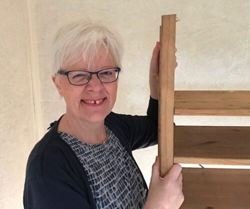 Katrin Gerke lacht und hält sich mit beiden Händen an einem Holzregal fest nach dem Umstellen der Möbel
