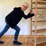 Katrin Gerke schiebt ein leeres Holzregal