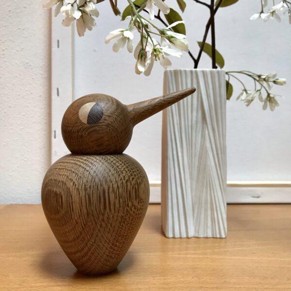 Ein rundlicher Holzvogel ausgeräucherten Eiche neben einer weißen Vintage-Vase mit dem Zweig einer blühenden Felsenbirne
