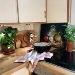 Küchenarbeitsplatte aus Holz, darauf Blumentöpfe mit frischen Kräutern, eine Keramik-Rürschüssel und ein Geschirrhandtuch