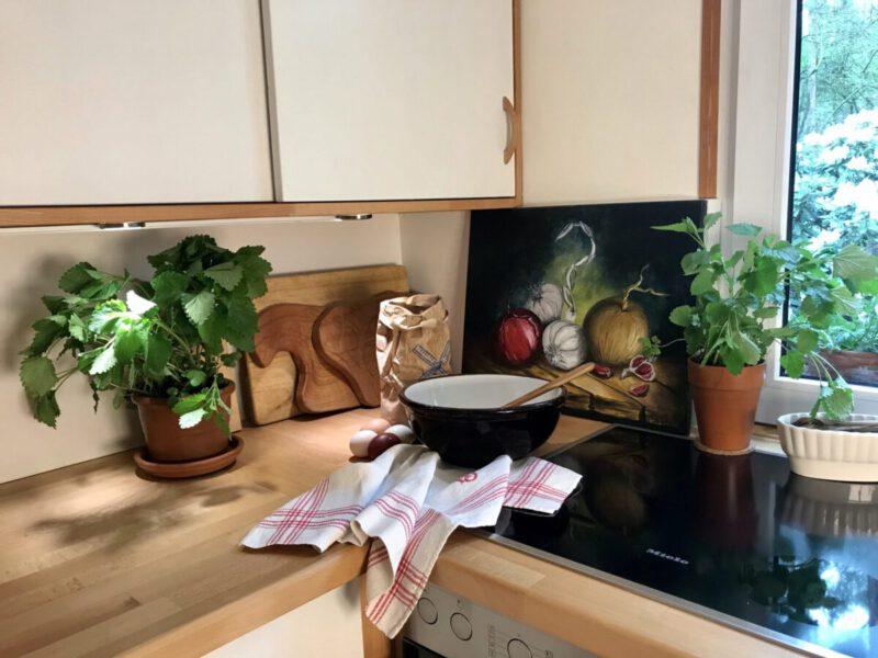 Küchenarbeitsplatte aus Holz, darauf zwei Blumentöpfe mit frischen Kräutern, einer Keramikschüssel und einem Geschirrtuch