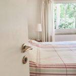 eine geöffnete weiße Tür gibt den Blick frei auf ein Bett, eine Nachttischlampe und ein Fenster