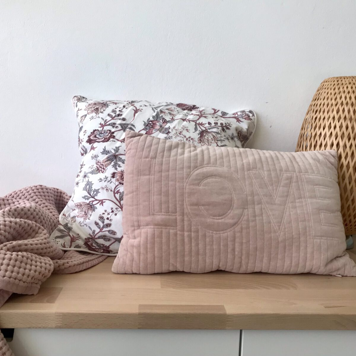 Zwei Kissen auf einem niedrigen Schrank, der mit einer Holzplatte als Bank genutzt werden kann.